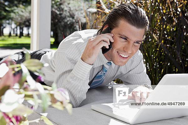 Kaufmann benutze ein Laptop und sprechen auf einem Mobiltelefon