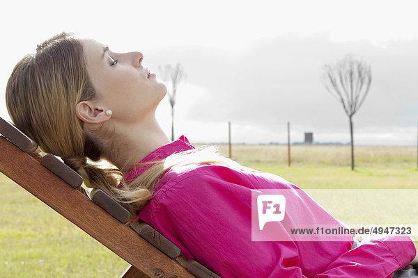 Geschäftsfrau entspannenden auf einer Chaiselounge in einem Feld