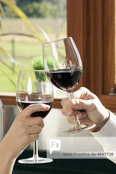 Paar stößt an mit Weingläser