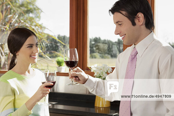 Paar stößt an mit Wein in der Küche