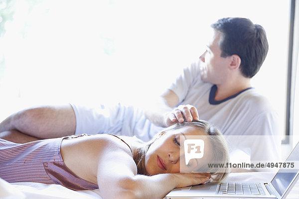 Frau mit ihrem Mann neben ihr auf dem Bett schlafen Frau mit ihrem Mann neben ihr auf dem Bett schlafen