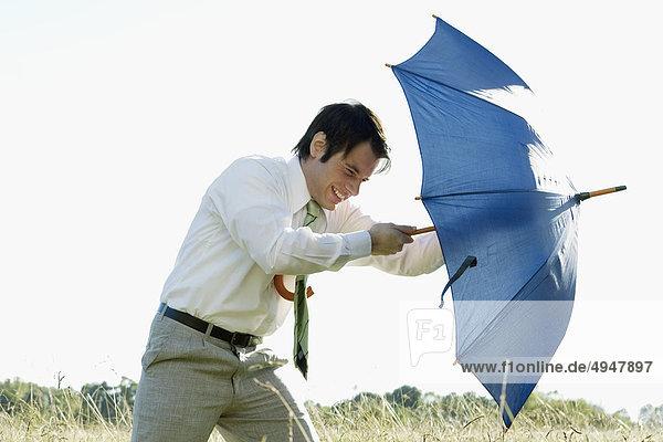 Unternehmer mit einem Regenschirm kämpfen