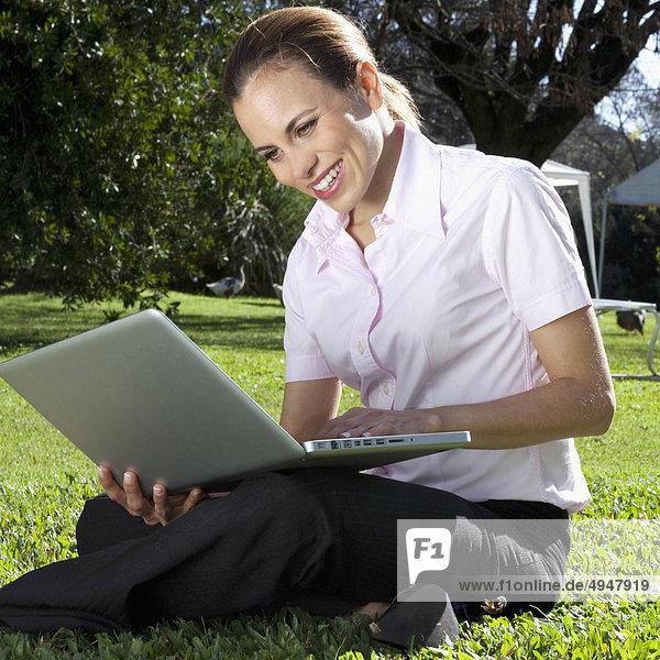 Geschäftsfrau mit einem Laptop in einem park