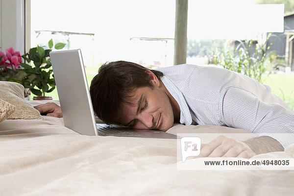 Mann mit einem Laptop auf dem Bett schlafen