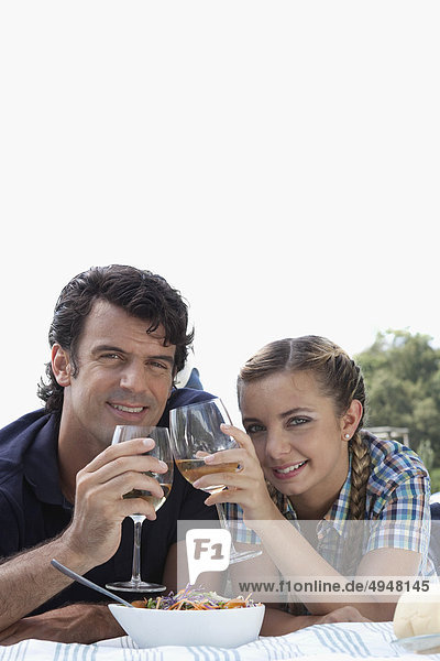 Paar stößt an mit Wein bei Picknick
