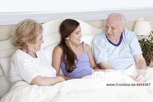Familie liegend im Bett und lächelnd