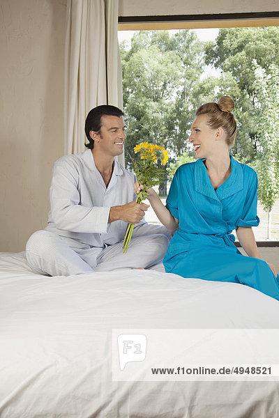 Mann geben Ehefrau Blume Bett