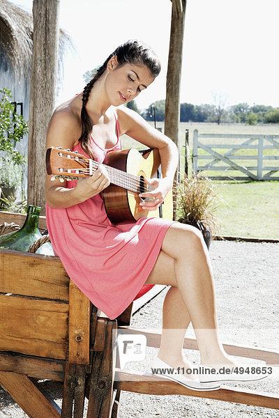 Frau eine Gitarre in einem park