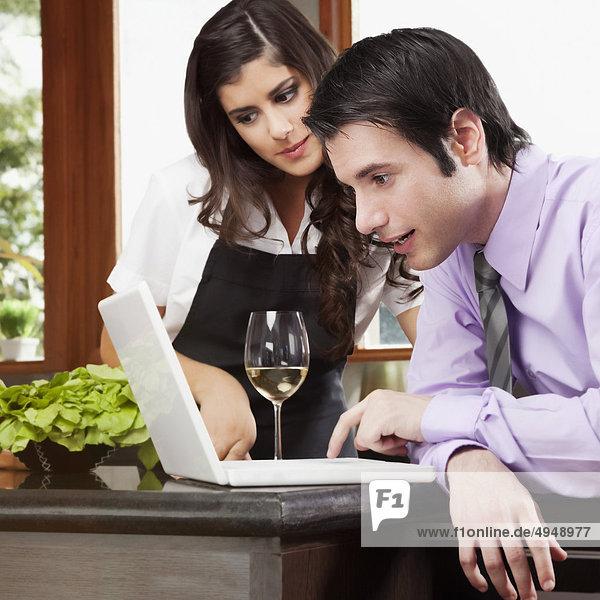 Paar mit einem Laptop in der Küche