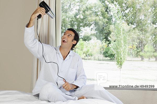 Mann  ein Haar Trockner und lächelnd hält
