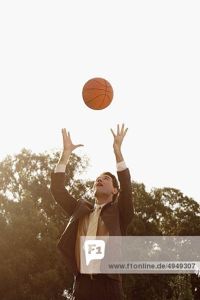 Kaufmann spielen mit ein Basketball in einem park Kaufmann spielen mit ein Basketball in einem park