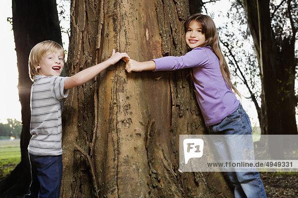 Junge und seine Schwester umarmt einen Baum in einem Garten Junge und seine Schwester umarmt einen Baum in einem Garten