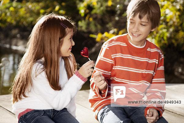 Boy geben ein Herz geformt Lollipop  ein Mädchen Boy geben ein Herz geformt Lollipop, ein Mädchen