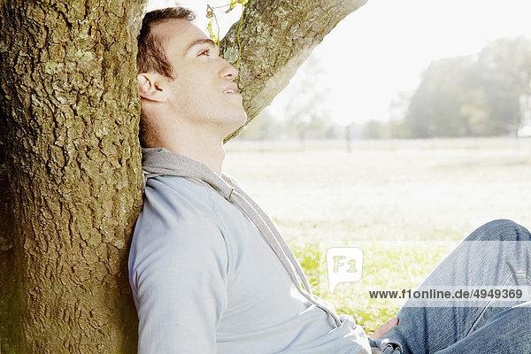 Mann  gegen einen Baum in einem Park sitzend Mann, gegen einen Baum in einem Park sitzend