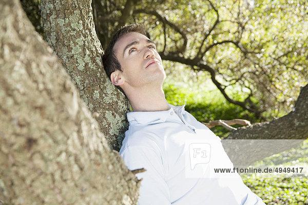 Sich gegen einen Baum in einem Park lehnend mann Sich gegen einen Baum in einem Park lehnend mann