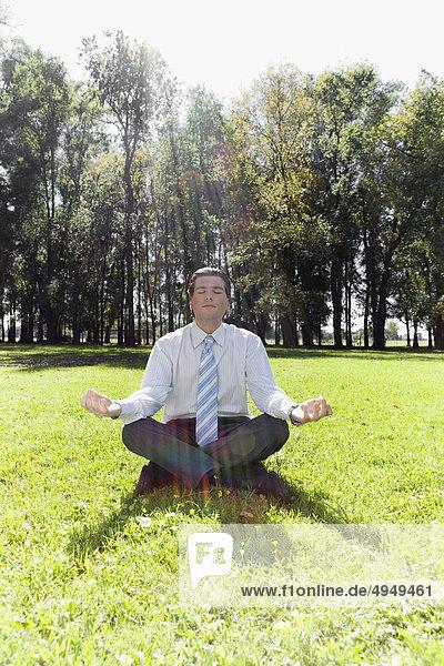 Kaufmann meditieren in einem park