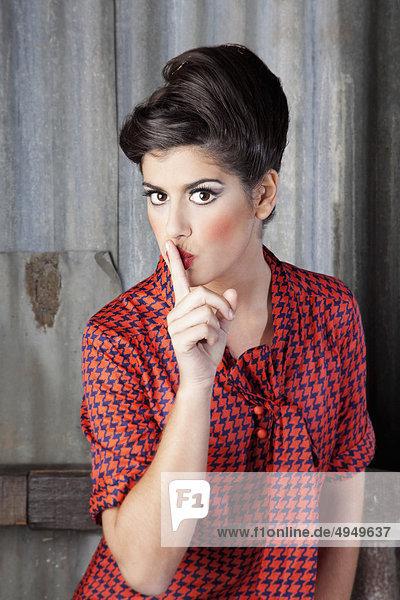 Portrait einer Frau mit Finger auf den Lippen Portrait einer Frau mit Finger auf den Lippen