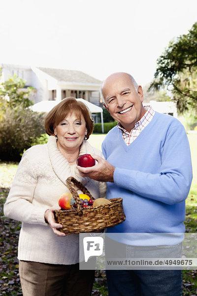 Paar halten einen Korb von Obst in einem park Paar halten einen Korb von Obst in einem park