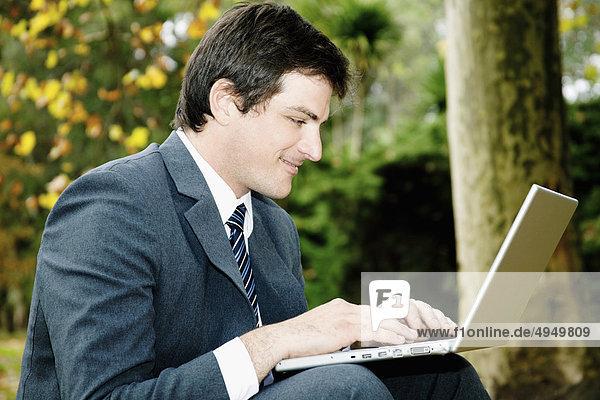 Unternehmer mit einem Laptop in einem park Unternehmer mit einem Laptop in einem park