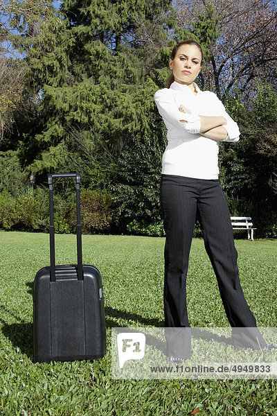 Geschäftsfrau stehend mit einem Koffer in einem park