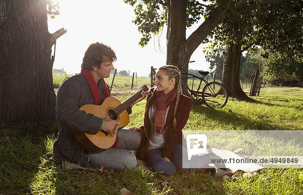 Man spielt Gitarre und eine Frau neben ihm sitzt