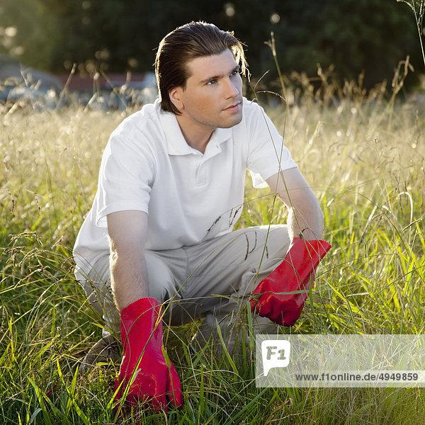 Mann hockend im Gras Mann hockend im Gras