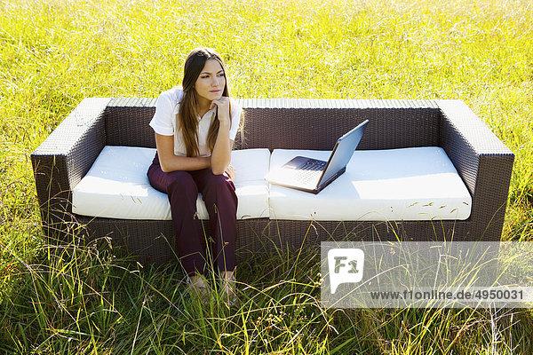 sitzend Geschäftsfrau Notebook Couch Wiese