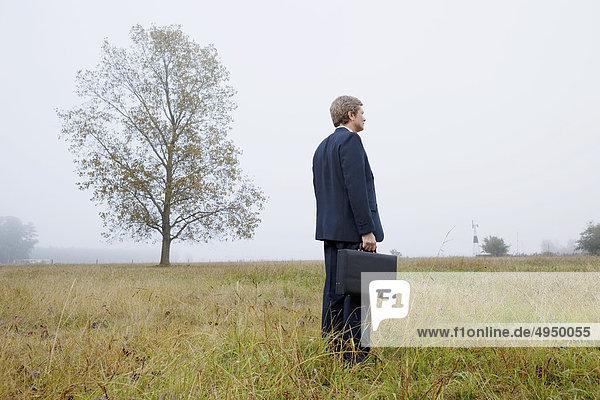 Geschäftsmann hält eine Aktentasche und stehen in einem Feld