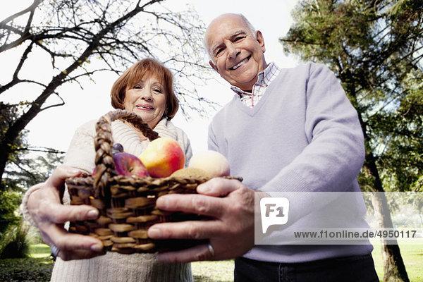 Paar halten einen Korb von Obst in einem park