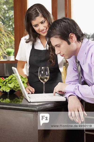 Paar mit einem Laptop in der Küche Paar mit einem Laptop in der Küche