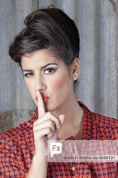 Portrait einer Frau mit Finger auf den Lippen mund