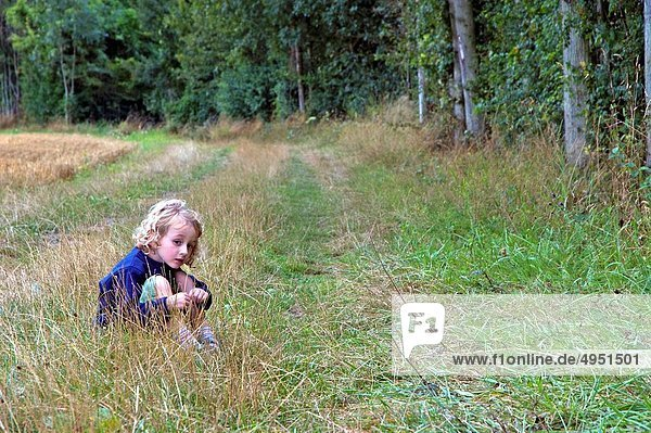 Four year old girl sitting alone in the grass beside a forest  France