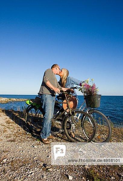reifes Paar Fahrradfahren am Strand und küssen