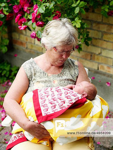 sitzend Wohnhaus halten frontal Großmutter Baby