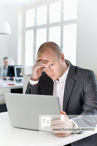 Mann sitzen in Büro Blick auf laptop