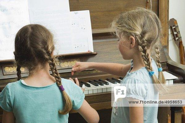 Zwei Mädchen  die Klavier spielen und Musik machen