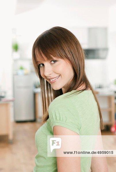 Frau in der Küche stehend  lächelnd