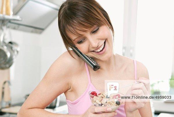 Frau isst Obstmüsli mit am Telefon