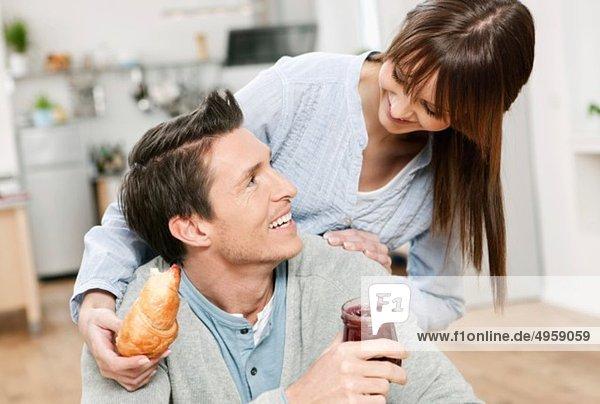 Mann und Frau in der Küche  Frau mit Croissant