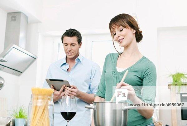 Mann und Frau bei der Zubereitung von Nudeln in der Küche