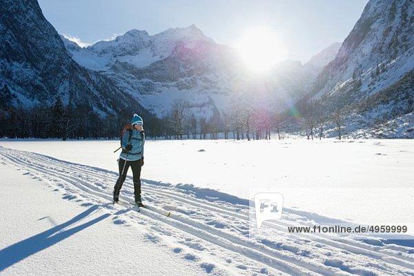 Seniorin beim Langlaufen mit Karwendalgebirge im Hintergrund