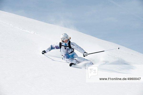 Österreich  Kleinwalsertal  Junge Frau beim Skifahren und Lächeln