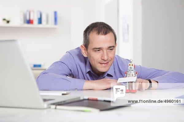 Deutschland  Bayern  München  Geschäftsmann im Büro  der mit Roboter spielt
