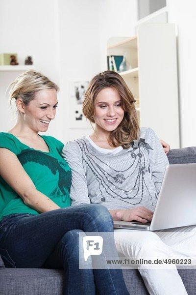 Deutschland  München  Junge Freunde zu Hause und am Laptop  lächelnd