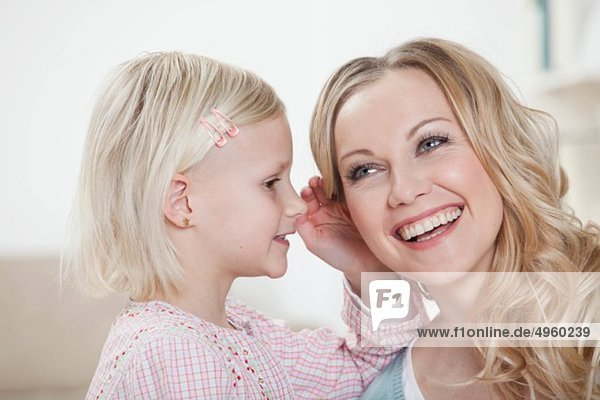 Germany  Bavaria  Munich  Daughter whispering in mother's ear  smiling
