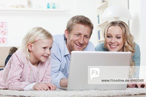 Germany  Bavaria  Munich  Family lying on carpet and using laptop  smiling