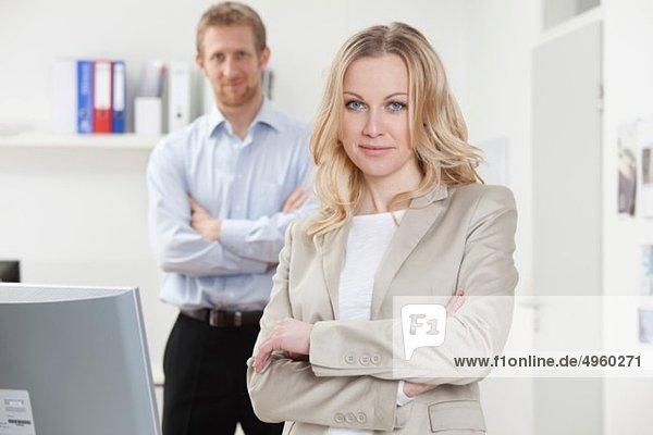 Geschäftsfrau und Geschäftsmann im Büro  lächelnd  Portrait
