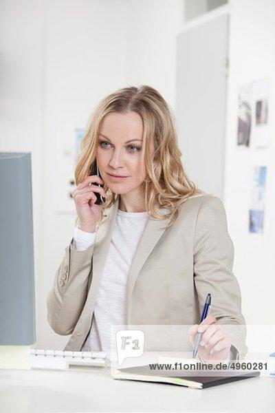 Geschäftsfrau am Handy im Büro