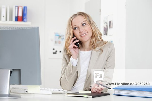 Geschäftsfrau am Handy im Büro  lächelnd