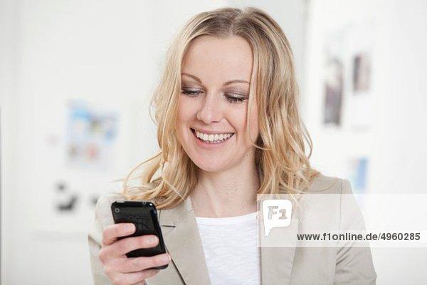 Geschäftsfrau mit Handy im Büro  lächelnd